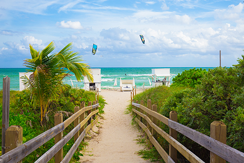 This is a stock photo. A pathway on to Miami Beach with the ocean in the background.