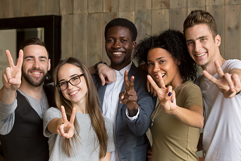 This is a stock photo. A diverse group of adults making a peace sign with their fingers.