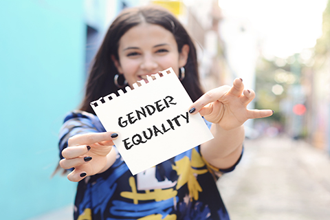 "This is a stock photo. A woman holding a sign which reads ""gender equality."""