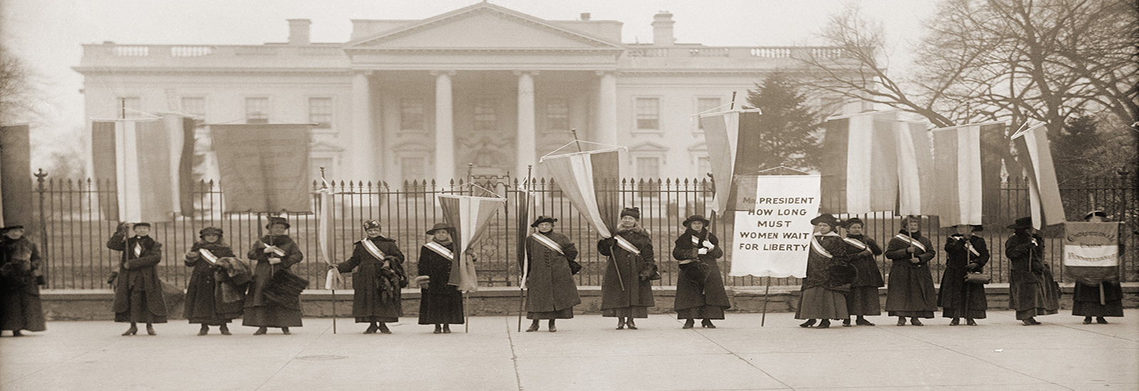 A historical stock photo of women suffragists protesting outside of the White House.