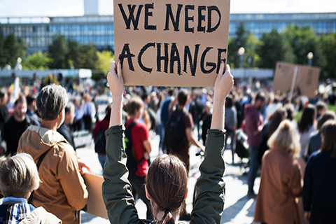 "A close up photo of a sign at a climate change protest. The sign reads, ""We Need A Change."""
