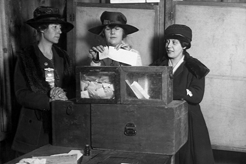 A historical 1917 photo of three women suffragists casting their vote at a ballot box. This image was obtained via Shutterstock.